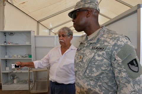 Dario Gonzalez, left, a medical director with the International Organization for Migration and a native of New York City, explains to Maj. Uzoma Aniniba, a Denver native, and the operations officer for the 36th Engineer Brigade, how the health care workers will archive the patients records electronically, after the grand opening ceremony of the Ebola treatment unit near Buchanan, Liberia, Dec. 22, 2014, as part of Operation United Assistance.  (Sgt. Ange Desinor 13th Public Affairs Detachment)