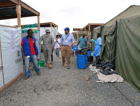 Andrew Lind, right, a San Mateo, Calif., native and a project coordinator for the International Organization for Migration, takes Soldiers of the 36th Engineer Brigade, out of Fort Hood, Texas, on a tour around the Ebola treatment unit after its grand opening, Buchanan, Liberia, Dec. 22, 2014, as part of Operation United Assistance. Lind showed the Soldiers the modifications that were made based off other ETUs. (Sgt. Ange Desinor 13th Public Affairs Detachment)