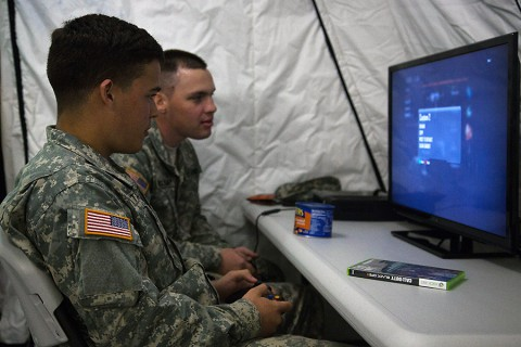 Pfc. Michael Matale and Spc. Britton McGlamy, both assigned to 101st Sustainment Brigade, 101st Airborne Division (Air Assault), plays a video game at the grand opening of the USO at Barclay Training Center, Monrovia, Liberia, Dec. 28, 2014.  (Spc. Rashene Mincy, 55th Signal Company)