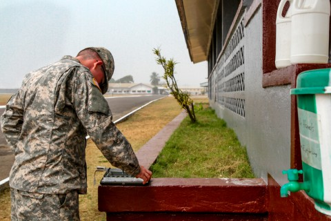 Spc. William Ferguson, native of Oklahoma City, Okla., health specialist for Headquarters Support Company, Headquarters and Headquarters Battalion, performs his routine check of the Heat Category wet-bulb thermometer, outside the Barclay Training Center medical building, Monrovia, Liberia, Jan. 12, 2015. Every hour Ferguson checks the temperature on camp to help prevent Soldier heat casualties, refills the bleach buckets and helps maintain the overall health of his fellow Soldiers while deployed for Operation United Assistance. Operation United Assistance is a Department of Defense operation in Liberia to provide logistics, training and engineering support to U.S. Agency for International Development-led efforts to contain the Ebola virus outbreak in western Africa.  (Spc. Caitlyn Byrne/U.S. Army)