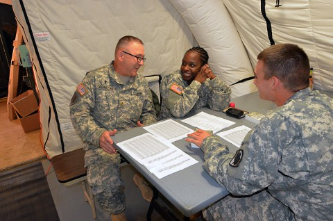 From left, Chaplain Maj. Alfred Grondski, a Trenton, N.J., native talks to Spc. Tamisha Cook, a Oviedo, Florida native, cable system installer/maintainer, both of Headquarters and Headquarters Company, 36th Engineer Brigade, and Pfc. Addison Cook, a Berryville, Arkansas native, cable system installer/maintainer, of 50th Signal Battalion, 35th Signal Brigade, out of Fort Bragg, South Carolina, about the upcoming new year during a prayer breakfast, at the National Police Training Academy, Payenesville, Liberia. Dec. 31, 2014, in support of Operation United Assistance. (Sgt. Ange Desinor 13th Public Affairs Detachment)