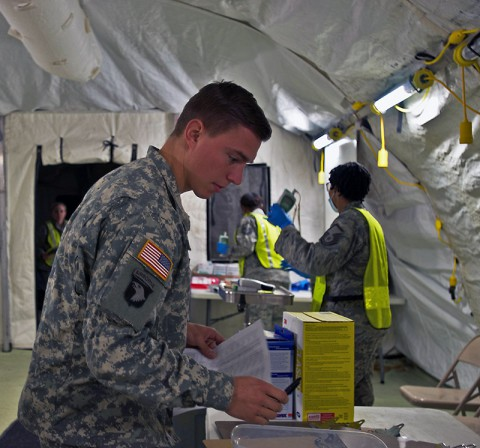First Lt. Dan Thueneman, executive officer, Intelligence and Sustainment Company, Headquarters and Headquarters Battalion, 101st Airborne Division (Air Assault), fills out the signs and symptoms checklist before he has his temperature taken, during his 21-day controlled monitoring period at Joint Base Langley – Eustis, Va., Jan. 20, 2015. (U.S. Army photo by Sgt. Matt Britton 27th Public Affairs Detachment/Released)