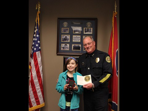 Clarksville Police Deputy Chief Parr presents Jenna King with the CPD Coin and the CPD Patch.