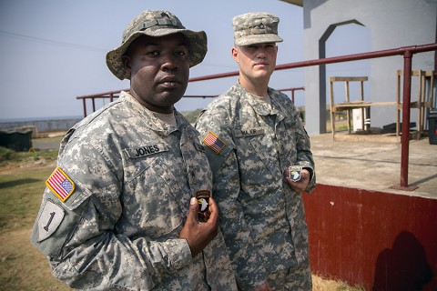 Sgt. Elijah Jones, left, a power generator equipment repairman, with the 82nd Civil Affairs Battalion, and Pfc. Michael Major, a wheeled vehicle mechanic with the 1st Area Medical Laboratory, hold the coins they received from Maj. Gen. Gary Volesky, Joint Forces Command – United Assistance commanding general, for being chosen as the service members of the week, Monrovia, Liberia, Jan. 30, 2015. (Staff Sgt. Terrance D. Rhodes, 101st Airborne Division Public Affairs)