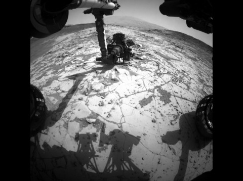 """This view from the wide-angle Hazard Avoidance Camera on the front of NASA's Curiosity Mars Rover shows the rover's drill in position for a mini-drill test to assess whether a rock target called """"Mojave"""" is appropriate for full-depth drilling to collect a sample. (NASA/JPL-Caltech)"""