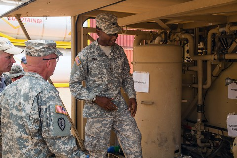 Spc. Darius Miles, right, a water treatment specialist, assigned to Task Force Lifeliner, 101st Sustainment Brigade, 101st Airborne Division (Air Assault), in support of Joint Forces Command – United Assistance talks about the process of water purification to Brig. Gen. Frank Tate, left, the deputy commanding general for support, JFC-UA Jan. 2, 2015, in Buchanan, Liberia. (Spc. Rashene Mincy, 55th Signal Company (Combat Camera))