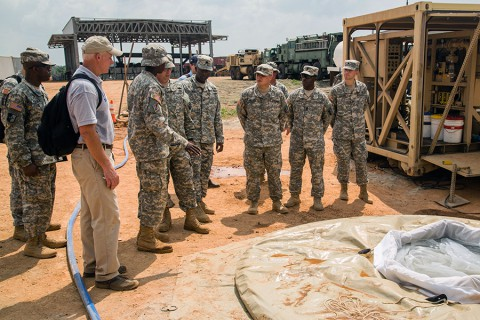 Members of Task Force Lifeliner, 101st Sustainment Brigade, 101st Airborne Division (Air Assault), in support of Joint Forces Command – United Assistance, show Brig. Gen. Frank Tate, the deputy commanding general for support, JFC-UA, the functions of a Tactical Water Purification System, Jan. 2, 2015, in Buchanan, Liberia.  (Spc. Rashene Mincy, 55th Signal Company (Combat Camera))