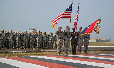 A joint color guard present arms, dipping the 101st Airborne Division (Air Assault) colors, during the playing of the national anthems of Liberia and the U.S. during the 101st's color casing ceremony held at the Barclay Training Center, Monrovia, Liberia, Feb. 26, 2015. The final color casing represents the completion of the Joint Forces Command - United Assistance mission in Liberia in support of Operation United Assistance. (Spc. Rashene Mincy, 55th Signal Company (Combat Camera))