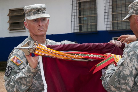 Col. Edward Bailey, commander of Task Force Eagle Medic and the 86th Combat Support Hospital based out of Fort Campbell, KY, cases his unit's colors during a ceremony at the National Police Training Academy, Paynesville, Liberia, Feb. 12, 2015. The 86th CSH, deployed as Task Force Eagle Medic in support of Operation United Assistance, will head back to Fort Campbell, KY.  (Sgt. 1st Class Nathan Hoskins, 101st Airborne Division Public Affairs)