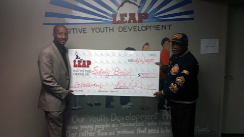 City Councilman Richard Garrett presents Sidney Brown with a check for $500.00.