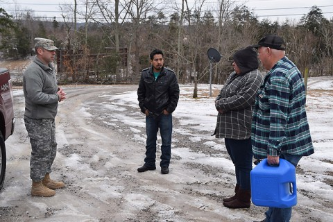 Maj. Colby Tippens delivers a can of kerosene to a family in need in Monterey, Tennessee.