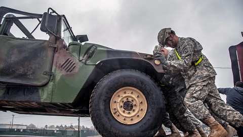 Soldiers from the 194th Military Police Company, 716th Military Police Battalion, supported on Fort Campbell by the 101st Sustainment Brigade, 101st Airborne Division, push a Humvee off of a tractor-trailer March 26th at Fort Campbell, KY. The 194th MP was one of several units that deployed to Africa that was taking part in a mission to receive equipment returning from the deployment. (Sgt. Leejay Lockhart, 101st Sustainment Brigade Public Affairs)
