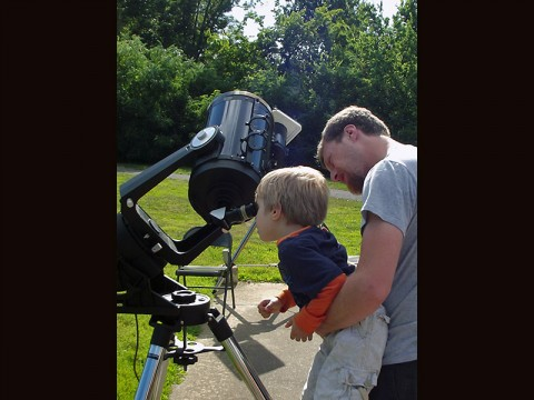 A child learning how to look through a telescope. (LBL Staff)