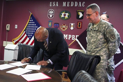 Blanchfield Army Community Hospital commander Col. George N. Appenzeller and Dr. Frank S. Royal Jr., Meharry Medical College's vice dean of clinical affiliations, sign a formal agreement Friday, creating a partnership for regular clinical rotations at the Fort Campbell hospital. (U.S. Army photo by Courtney Wittmann)