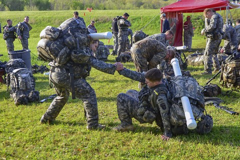 Second Lt. Ryan Jesse assists his teammate, 1st Lt. Jonathan Pantano, is getting on his feet to complete a five-mile ruck march during day one of the Best Sapper Competition at Fort Leonard Wood, Mo., April 21, 2015. Jesse and Pantano, both engineers, represented the 326th Brigade Engineer Battalion, 1st Brigade Combat Team, 101st Airborne Division (Air Assault), in this year's competition. (Sgt. Samantha Parks, 1st Brigade Combat Team, 101st Airborne Division (Air Assault) Public Affairs)