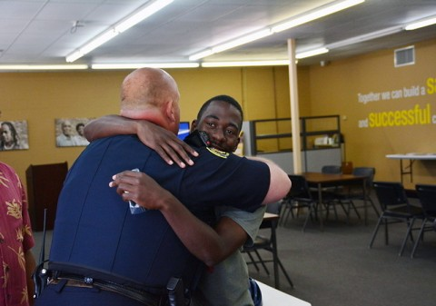 Jaquez Willis hugs CPD Officer Jeff Derico after receiving his bicycle.