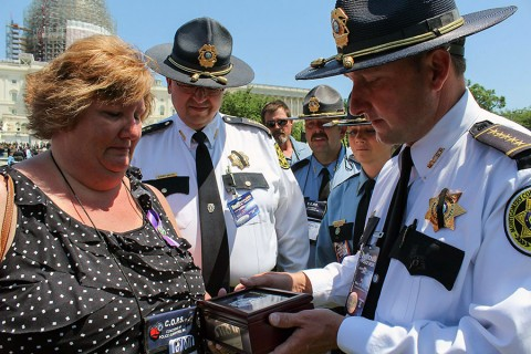 Montgomery County Sheriff John Fuson presents Jennifer Johnson with a badge given to the family by the National Sheriff's Association. (MCSO)