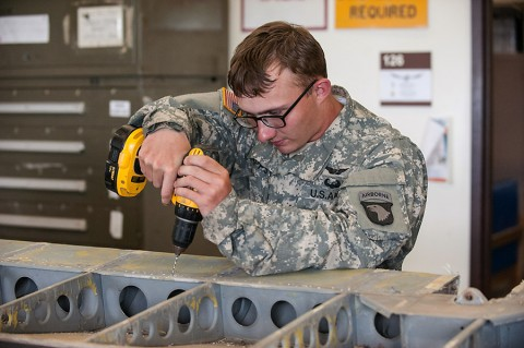 Pfc. Jacob Capps, an airframe structural repair specialist with Company B, 96th Aviation Support Battalion, 101st Combat Aviation Brigade, 101st Airborne Division, drills to enlarge holes in the metal of an aileron of a C-47 Skytrain, here, May 18, 2015. Sheet metal will replace canvas, and drilling the holes ensure that the replacement rivets will fit properly when installed. (Sgt. Duncan Brennan, 101st CAB, 101st Airborne Division (Air Assault) Public Affairs)