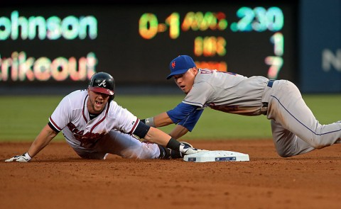 Atlanta Braves Chris Johnson (23) slides safely into second base ahead of the tag by New York Mets shortstop Wilmer Flores (4) on a fielding error in   the fourth inning of their game at Turner Field. (Jason Getz-USA TODAY Sports)