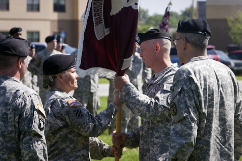 During a relinquishment of command ceremony Thursday, Lt. Col. Bryan J. Walrath accepts the Warrior Transition Battalion colors from Command Sgt. Maj. Staci Rea. The battalion's executive officer, Maj. Jamey Turner will serve as interim commander. (U.S. Army photo by David E. Gillespie)