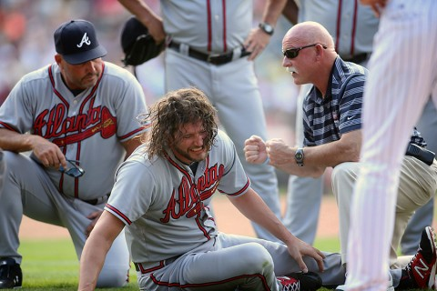 Atlanta Braves relief pitcher Jason Grilli (center) is attended to by Atlanta Braves manager Fredi Gonzalez (left) and team trainer Jeff Porter   (right), and teammates after being injured during the ninth inning against the Colorado Rockies at Coors Field. The Rockies won 3-2. (Chris   Humphreys-USA TODAY Sports)