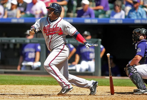 Atlanta Braves third baseman Juan Uribe (2) hits a single during the fourth inning against the Colorado Rockies at Coors Field. The Rockies won   3-2. (Chris Humphreys-USA TODAY Sports)