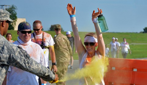 Spc. Danielle Cooper, 1st Battalion, 506th Infantry Regiment, 1st Brigade Combat Team, 101st Airborne Division (Air Assault), and her husband, Michael Cooper, are blasted with yellow-dyed corn starch at the one-mile mark of the color run here July 18, 2015. The color run took place as part of the Eagle Challenge Fitness Tour. (Staff Sgt. Sierra Fown 2nd Brigade Combat Team, 101st Airborne Division (AA) Public Affairs)