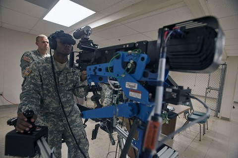 Sgt. Jarrod Stegall, a vehicle crew member with the 626th Brigade Support Battalion, 3rd Brigade Combat Team, 101st Airborne Division, scans for targets during a simulated convoy here July 16, 2015. Stegall conducted training on the 3rd Brigade Combat Team's unstabilized gunnery trainer-individual, the first of its kind in the active component Army, which allows unit master gunners to build scenarios for crew gunners to virtually engage targets and validate them before conducting live-fire gunnery tables. (Staff Sgt. Joel Salgado, 3rd Brigade Combat Team Public Affairs)
