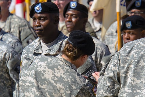 """Col. Kimberly J. Daub, commander of the 101st Airborne Division (Air Assault) Sustainment Brigade, places the """"Old Abe"""" 101st Airborne Division patch on Lt. Col. Able E. Young, the commander of the 129th Combat Sustainment Support Battalion, July 30, 2015, at Fort Campbell, Ky. The """"Lifeliners"""" Brigade uncased new colors and donned the division patch in a ceremony to symbolize the brigade's re-designation as the 101st Airborne Division (Air Assault) Sustainment Brigade. (Spc. Joseph Green, 101st Sustainment Brigade, 101st Airborne Division (Air Assault) Public Affairs)"""