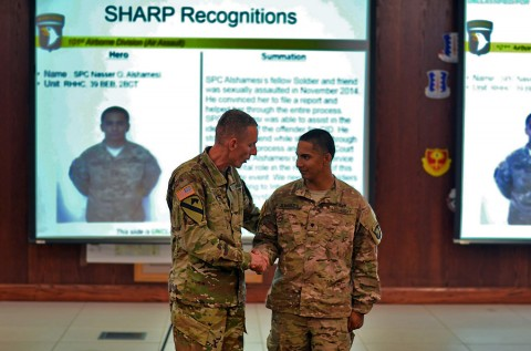Spc. Nasser O. Al-Shamesi, a chemical specialist for Headquarters and Headquarters Company, 39th Brigade Engineer Battalion, 2nd Brigade Combat Team, 101st Airborne Division (Air Assault) receives a coin from Maj. Gen. Gary J. Volesky, commanding general of the 101st Airborne Division (Air Assault), at the division headquarters here, Aug. 20, 2015. Al-Shamesi played an integral role in assisting a fellow Strike Soldier through the SHARP reporting process following an incident that occurred in November 2014. (Staff Sgt. Sierra A. Fown, 2nd Brigade Combat Team, 101st Airborne Division (Air Assault) Public Affairs)