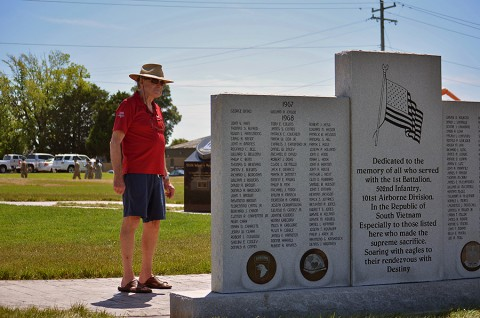 """A veteran takes time to read one of the 2nd Brigade Combat Team, 101st Airborne Division (Air Assault) memorials shortly after a rededication ceremony conducted by the """"Strike"""" brigade at Fort Campbell, Ky., during the Day of the Eagles, July 30, 2015. The event moved the memorials to the intersection of Screaming Eagle Blvd. and Tennessee Ave., across from Gear-To-Go. (Staff Sgt. Sierra A. Fown, 2nd Brigade Combat Team, 101st Airborne Division Public Affairs)"""
