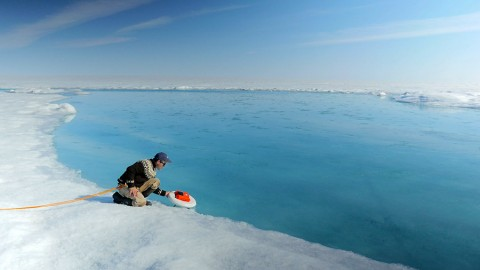 Laurence Smith (University of California, Los Angeles) deploys an autonomous drift boat equipped with several sensors in a meltwater river on the Greenland ice sheet. (NASA's Goddard Space Flight Center/Jefferson Beck)