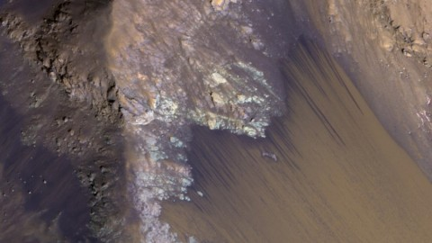 Among the many discoveries by NASA's Mars Reconnaissance Orbiter since the mission was launched on Aug. 12, 2005, are seasonal flows on some steep slopes, possibly shallow seeps of salty water. This July 21, 2015, image from the orbiter's HiRISE camera shows examples within Mars' Valles Marineris. (NASA/JPL-Caltech/Univ. of Arizona)