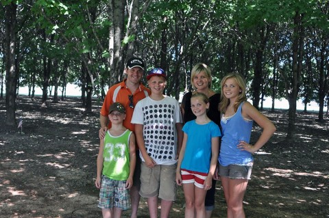 Janice Nikkel stands at the Gander Memorial Site at Fort Campbell, Ky., with her husband and children 25 years after the trees she donated were planted in 2010. When Nikkel was 15, she donated $20 in order to have one tree planted for every life lost during the Gander crash. (Courtesy photo)