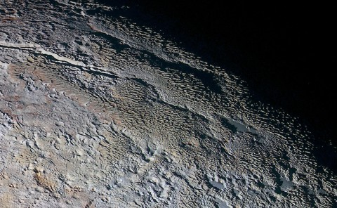 In this extended color image of Pluto taken by NASA's New Horizons spacecraft, rounded and bizarrely textured mountains, informally named the Tartarus Dorsa, rise up along Pluto's day-night terminator and show intricate but puzzling patterns of blue-gray ridges and reddish material in between. This view, roughly 330 miles (530 kilometers) across, combines blue, red and infrared images taken by the Ralph/Multispectral Visual Imaging Camera (MVIC) on July 14, 2015, and resolves details and colors on scales as small as 0.8 miles (1.3 kilometers). (NASA/JHUAPL/SWRI)
