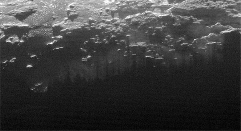Near-Surface Haze or Fog on Pluto: In this small section of the larger crescent image of Pluto, taken by NASA's New Horizons just 15 minutes after the spacecraft's closest approach on July 14, 2015, the setting sun illuminates a fog or near-surface haze, which is cut by the parallel shadows of many local hills and small mountains. (NASA/JHUAPL/SwRI)