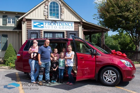 A family receives a car gift from Providence Auto Group, one of 19 giveaways the dealership has executed since inception in 2012.