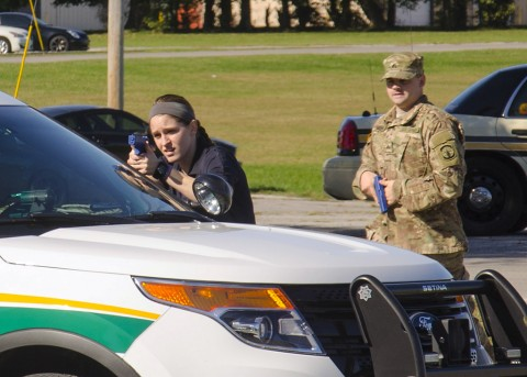 Officer Shelby Nelson with the Clarksville Police Department, provides cover for Sgt. John Michl, a military police officer with the 551st Military Police Company, 716th Military Police Battalion, 101st Airborne Division Sustainment Brigade, 101st Airborne Division (Air Assault), from behind a Montgomery County Sheriff's Office vehicle during the approaches and breaching portion of the Advanced Law Enforcement Rapid Reaction Training train-the-trainer active shooter course Oct. 14, 2015, at Fort Campbell, KY. (Spc. Joseph Green, 101st Sustainment Brigade, 101st Airborne Division (AA) Public Affairs)