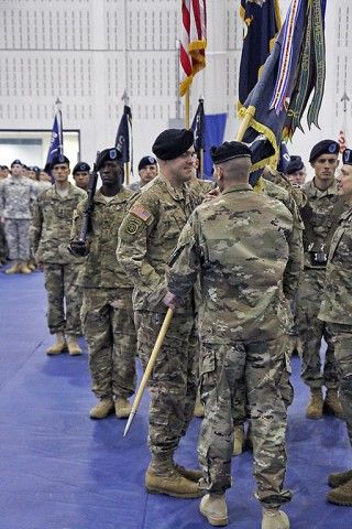 """Lt. Col. David Waters, commander of 1st Battalion, 506th Infantry Regiment, 1st Brigade Combat Team, 101st Airborne Division (Air Assault), passes the guidon to Command Sgt. Maj. James Brasher, the incoming """"Red Currahee"""" command sergeant major, during the change of responsibility ceremony Dec. 1, 2015 at Sabo Gym. Passing the guidon from the outgoing command sergeant major to the incoming is a tradition that signifies the transfer of responsibility within the battalion. (Sgt. Samantha Stoffregen, 1st Brigade Combat Team, 101st Airborne Division (Air Assault) Public Affairs)"""