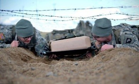 """Two medics with the 1st Battalion, 502nd Infantry Regiment, 2nd Brigade Combat Team, 101st Airborne Division, drag a litter while low crawling through barbed wire at Fort Campbell, Ky., Jan. 13, 2016, as part of the battalion's best medic competition. The competition, formally titled """"Talon Best Medic Competition,"""" was a two-day event that tested the limits and skills of a talon combat medic team. (Staff Sgt. Sierra A. Fown, 2nd Brigade Combat Team, 101st Airborne Division (Air Assault) Public Affairs)"""