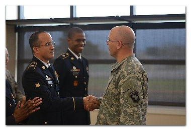 Sgt. Maj. Jesse E. Ruth, G1 sergeant major, 101st Airborne Division (Air Assault) presents a coin to Spc. David Rosario, 1st Squadron, 75th Calvary Regiment, 2nd Brigade Combat Team, 101st Airborne Division (Air Assault) following his selection of the division's AG Soldier of the quarter. (U.S. Army Staff Sgt. Sierra A. Fown, 2nd Brigade Combat Team, 101st Airborne Division (Air Assault) Public Affairs)