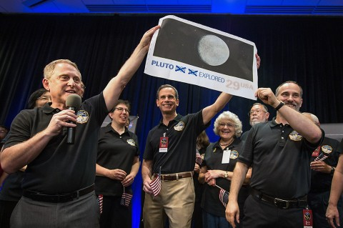Pluto Explored. (left to right): New Horizons Principal Investigator Alan Stern of Southwest Research Institute (SwRI), Boulder, Colorado; New Horizons' Deputy Project Scientist Leslie Young, SwRI; Johns Hopkins University Applied Physics Laboratory (APL) Director Ralph Semmel; Annette Tombaugh, daughter of Clyde Tombaugh, who discovered Pluto in 1930; and New Horizons Co-Investigator Will Grundy, Lowell Observatory, Flagstaff, Arizona hold a print of the 1991 Pluto stamp –with their suggested update – on July 14 at APL in Laurel, Maryland. (NASA/Bill Ingalls)