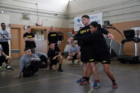 Sgt. 1st Class Liela Cowhig, a senior instructor for the Master Fitness Training Course, demonstrates how to position a Soldier before lifting him during an MFTC at Fort Campbell, Ky., Jan. 26, 2016. Cowhig and the other MFTC instructors spent two weeks at Fort Campbell teaching 101st Airborne Division (Air Assault) Soldiers about nutrition and exercise science. (Sgt. William White, 101st Airborne Division Public Affairs)