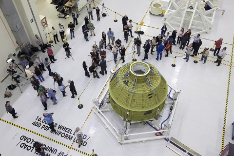 Inside the Neil Armstrong Operations and Checkout Building high bay at NASA's Kennedy Space Center in Florida, members of the news media get an up-close look at the Orion crew module pressure vessel on Feb. 3. Testing and assembly has begun, which will lead to Exploration Mission-1 in 2018. EM-1 will be an uncrewed flight test in which the spacecraft will launch atop NASA's Space Launch System rocket. (NASA/Bill White)