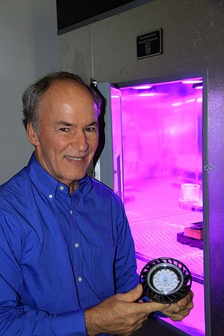 Dr. Ray Wheeler, lead for Advanced Life Support Research activities at Kennedy Space Center, holds a red and blue LED light fixture inside a laboratory at the Space Station Processing Facility. The LED lights recently were used to study the effects of different ratios of red and blue light on plant growth and development. (NASA/Jim Grossmann)