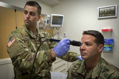 In a demonstration of the Telehealth process at Fort Campbell's Blanchfield Army Community Hospital, clinical staff nurse 1st Lt. Maxx P. Mamula examines mock patient Master Sgt. Jason H. Alexander using a digital external ocular camera. The image is immediately available to Lt. Col. Kevin A. Horde, a provider at Fort Gordon's Eisenhower Medical Center, offering remote consultation. (U.S. Army photo by David E. Gillespie)