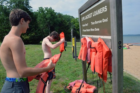 Two young swimmers place life vests from the Life Jacket Loaner board at the Cheatham Dam beach area in Ashland City, Tennessee. (Mark Rankin, U.S. Army Corps of Engineers, Nashville District)