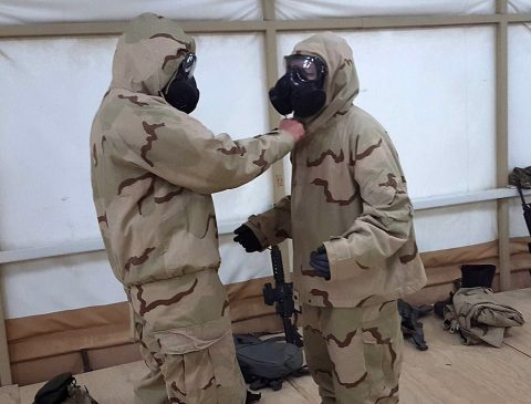 Two personnel from Task Force Strike practice proper Joint Service Lightweight Integrated Suit Technology (JSLIST) removal procedures at a training and logistical camp in southwest Asia, May 11, 2016. (1st Lt. Daniel I. Johnson)