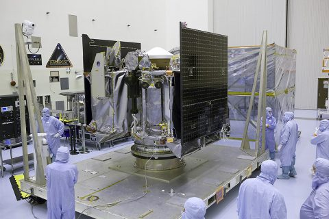 NASA's OSIRIS-REx spacecraft is revealed after its protective cover is removed inside the Payload Hazardous Servicing Facility at Kennedy Space Center in Florida. The spacecraft traveled from Lockheed Martin's facility near Denver, Colorado to Kennedy to begin processing for its upcoming launch, targeted for Sept. 8 aboard a United Launch Alliance Atlas V rocket. (NASA/Dimitri Gerondidakis)