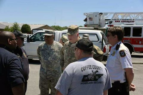 Tennessee's Adjutant General, Maj. Gen. Max Haston and Col. Milton Thompson, Commander, 30th Troop Command, discuss point of distribution operations for food and water with the Chief, Manchester Fire Dept., Director, Coffee County Homeland Sec., and the Director of Emergency Medical Services for Coffee County.